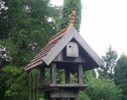 bird table with tiled roof and gargoyle finial thumb