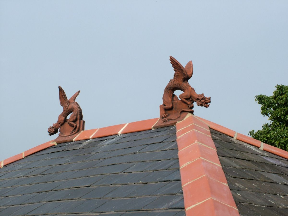 Winged dragon finials installed on a hip end roof